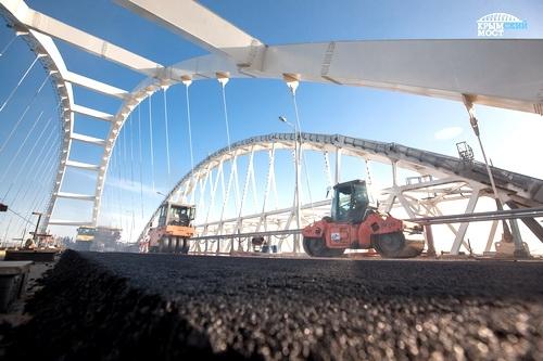 Строители асфальтируют полотно автодорожной арки Крымского моста